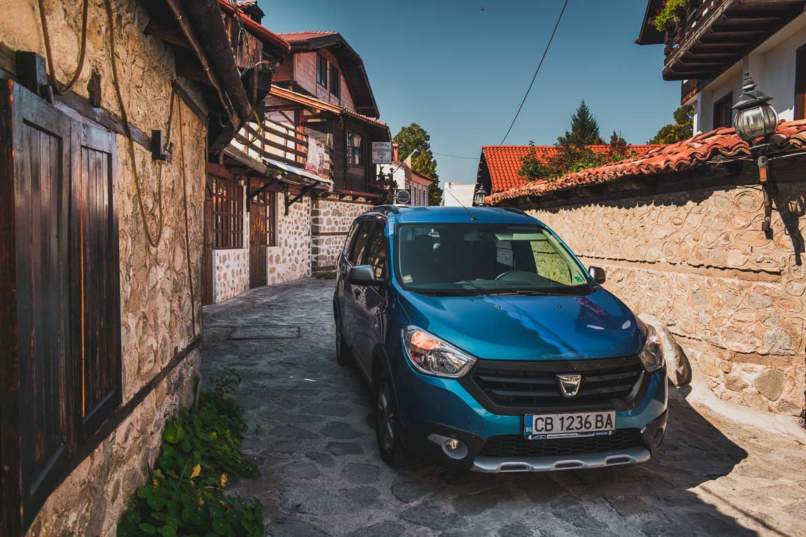 This photo shows our private airport transfer car outside the guesthouse we stayed at in Bansko Old Town. Hoppa airport transfers. How to get from Sofia to Bansko Bulgaria.