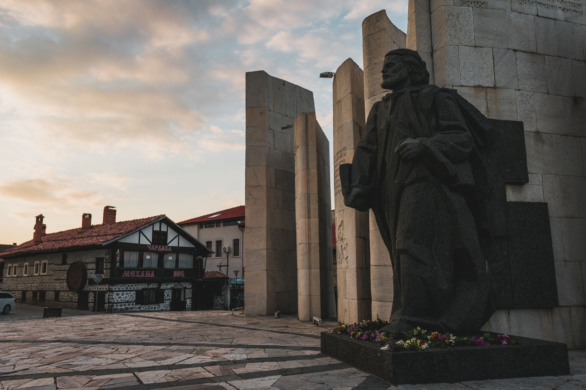 This photo shows Paisii Hilendarski monument in Bansko main square. Hoppa airport transfers. How to get from Sofia to Bansko Bulgaria.