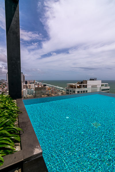 This photo shows the infinity pool at Mövenpick Hotel Colombo. We can see tall buildings and the Indian Ocean in the background.