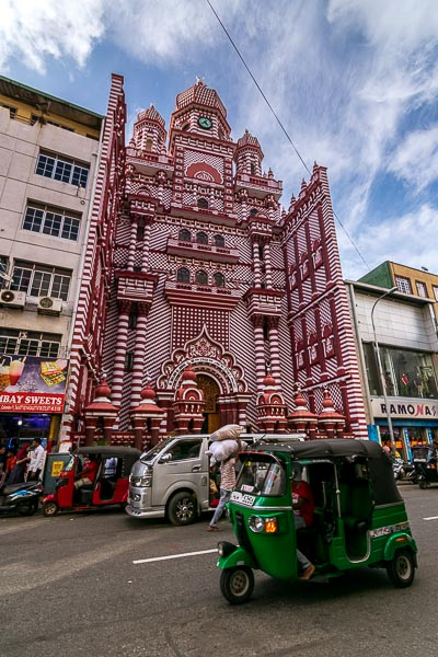 This is a photo of Jami Ul-Alfar Mosque on a busy day. There are people, cars and tuk tuks in front of it. However, it is very impressive with its red and white colour scheme.