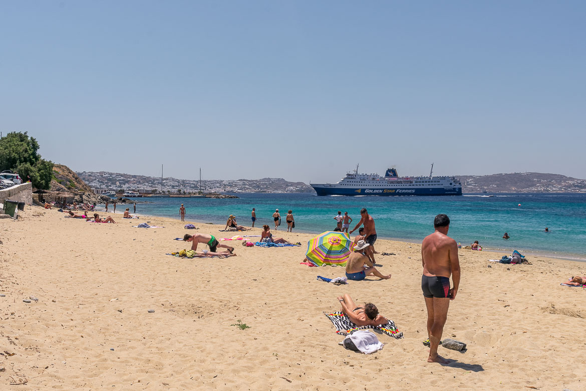 This is an image of Agios Stefanos beach. There are quite a few people sunbathing on the sandy beach while a ferry sails towards the island's port next door. In the background, we can see Mykonos Town.