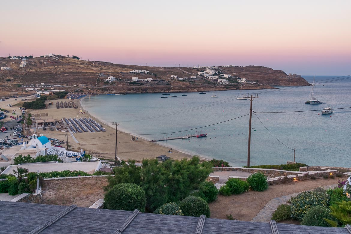 This is a panoramic shot of Kalo Livadi beach at sunset. There are 3 large beach clubs on the sandy beach. There are also a handful of yachts in the sea.