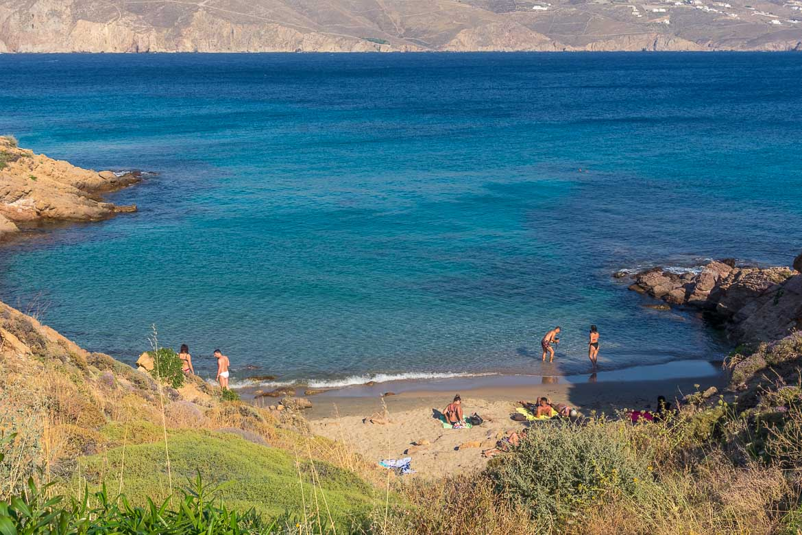 This image shows the tiny beach near Kiki's Tavern. It is a secluded hidden cove with crystal clear blue waters. Less than 10 people are on the beach and in the water.