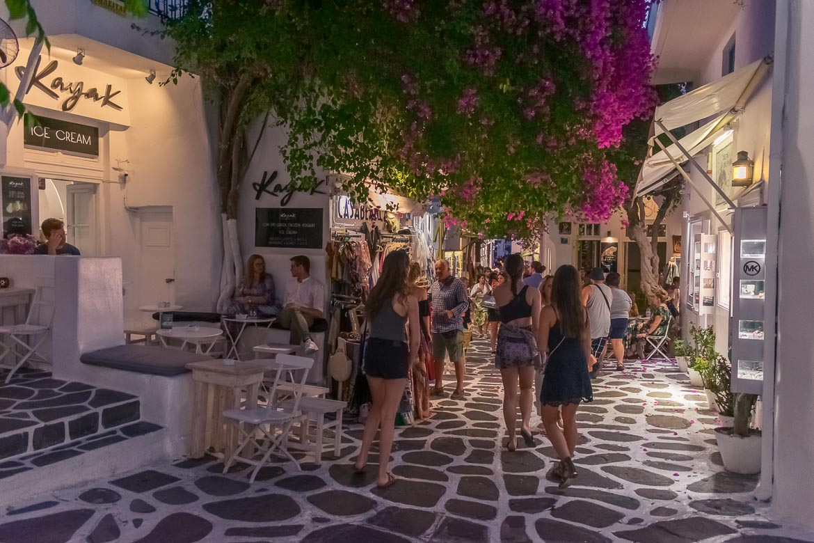 This image shows a busy street in Mykonos Chora in the evening. Many people walk along the street and there is also a huge bougainvillea above them.