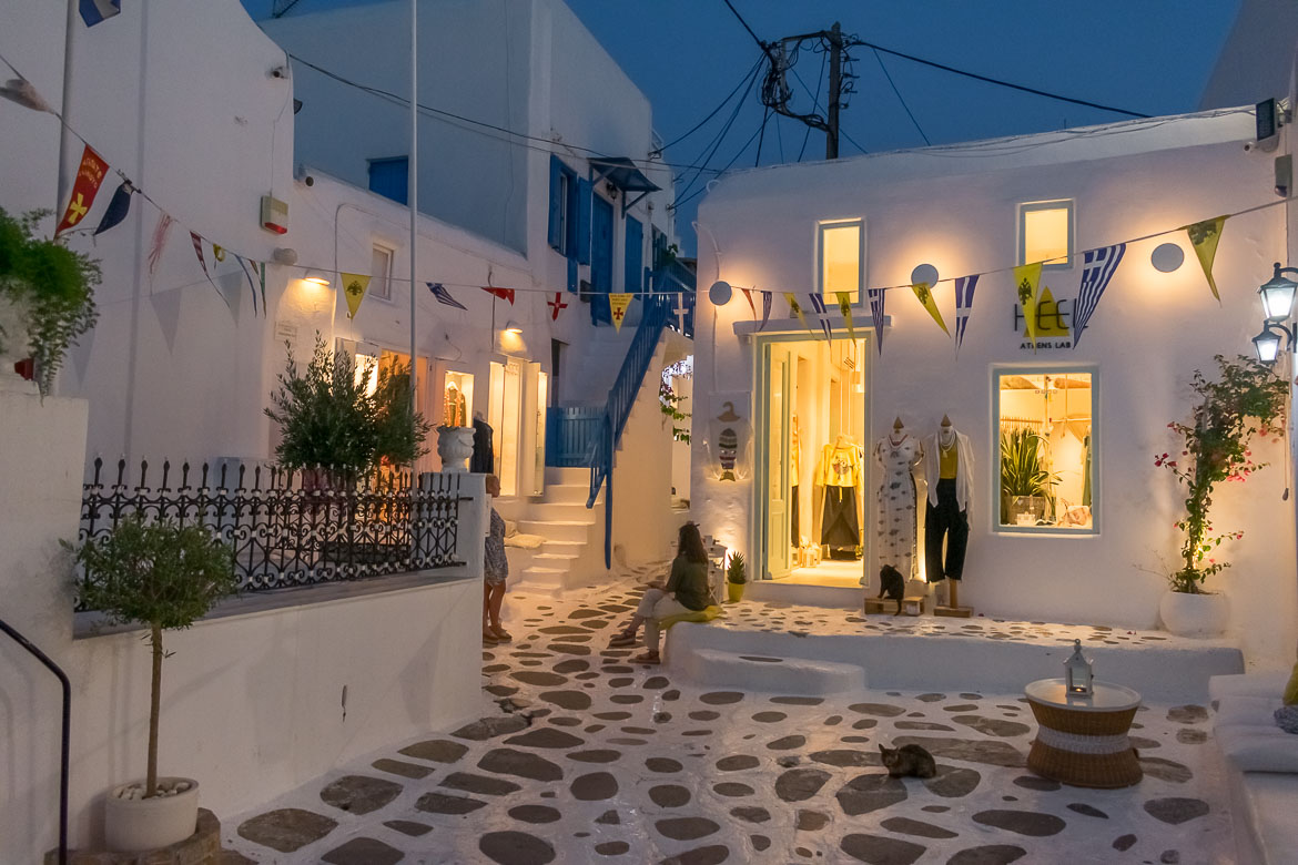 This photo shows a whitewashed street in Chora in the evening. There are two women chatting and a couple of cats hanging around outside a shop but other than that the scene is very peaceful.