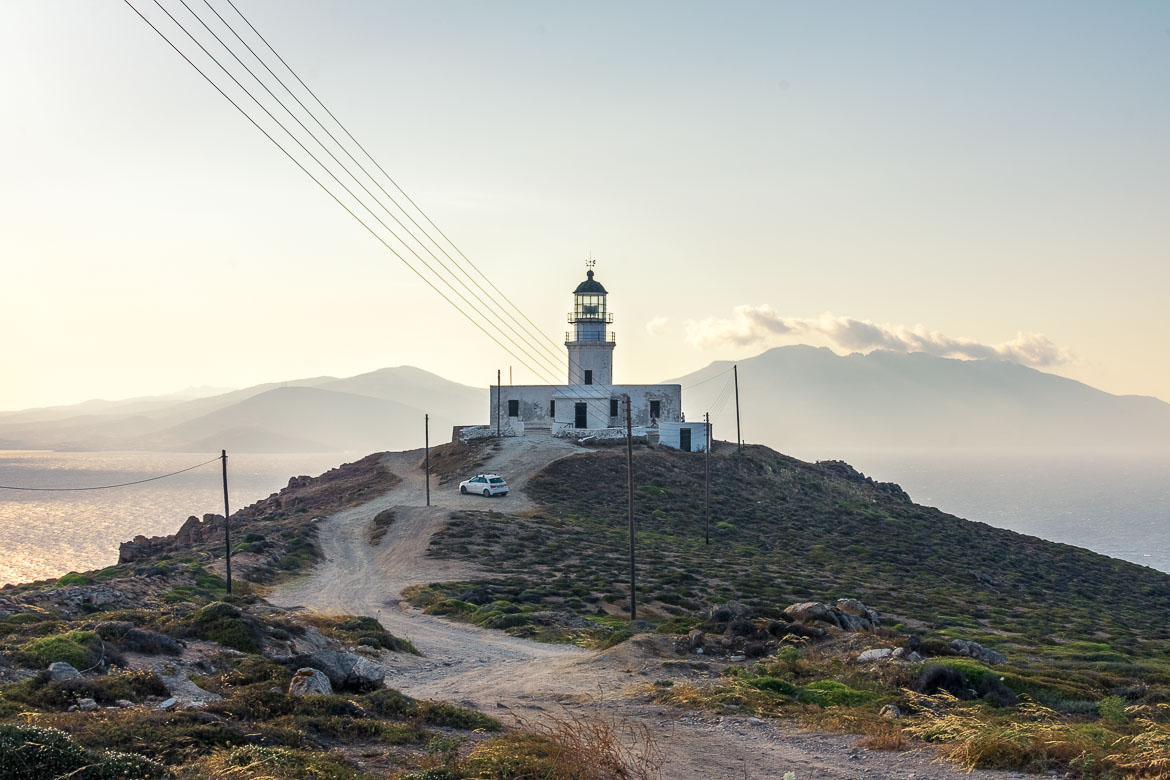 This is an image of Armenistis Lighthouse standing gloriously on a hill overlooking the sea.