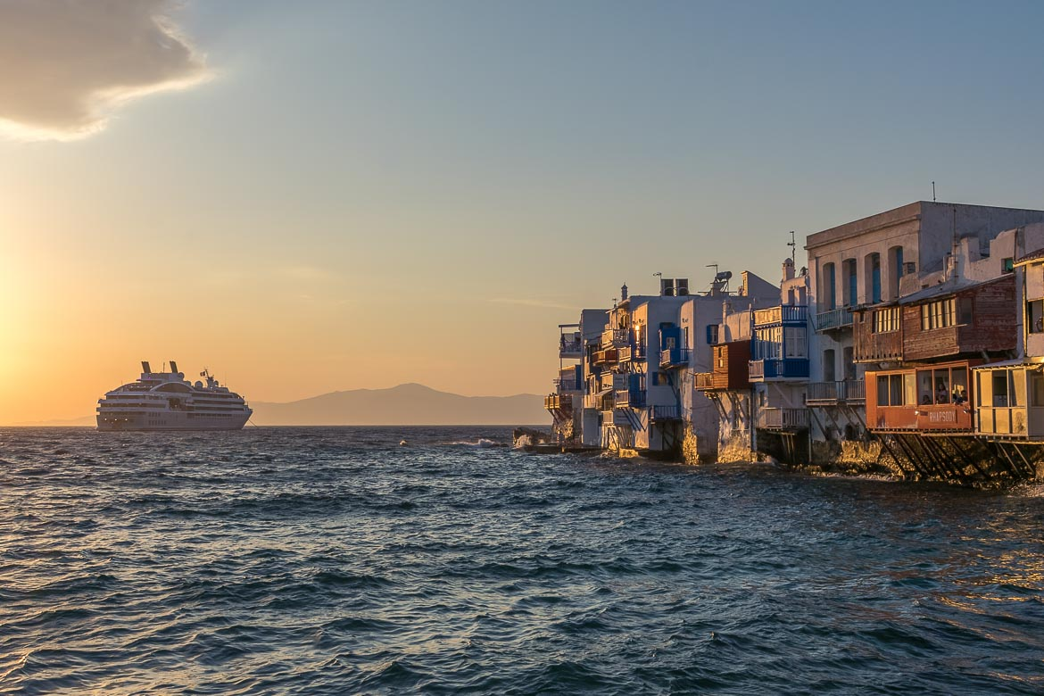 This image shows the row of beautiful buildings of Little Venice at sunset. The walls are painted gold and there is a cruise ship in the background. Watching the sunset at Little Venice is among the things you add to your 3 days in mykonos itinerary.