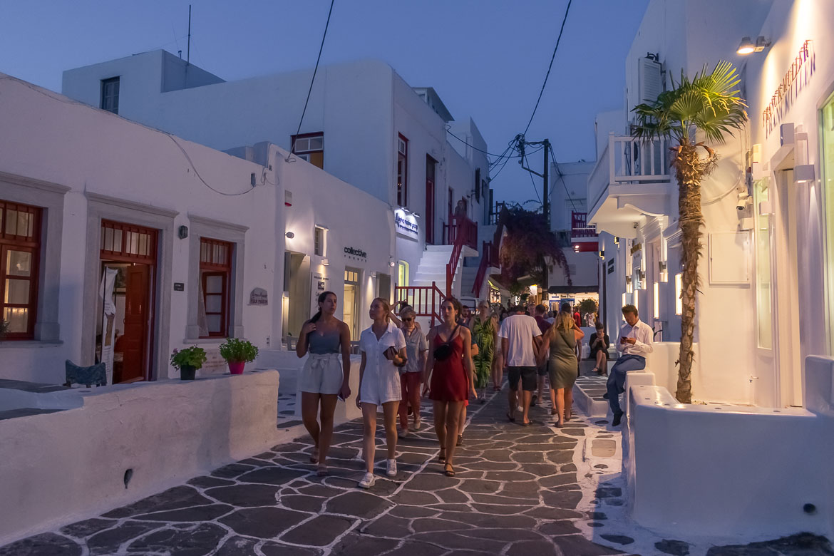 This is a photo of Matoyianni Street in the evening. There are many people walking along the street, which is lined with brightly lit shops.