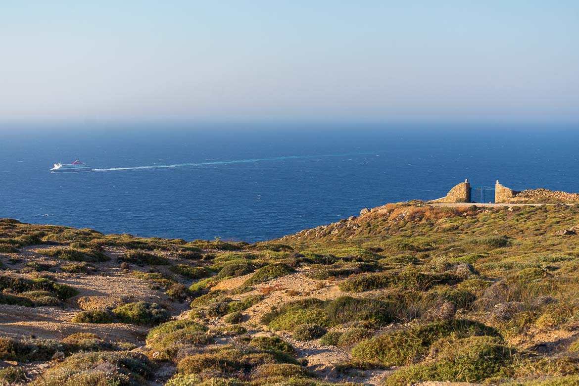 This is a photo of an unspoilt hill in Mykonos overlooking the sea. There is a ferry in the sea.