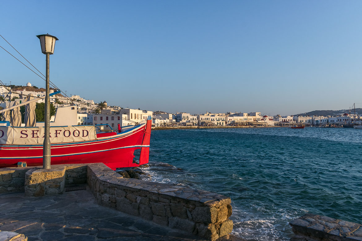 This photo shows a bright red traditional boat in Mykonos Old Port. In the background, Chora looks lovely as the sun goes down.