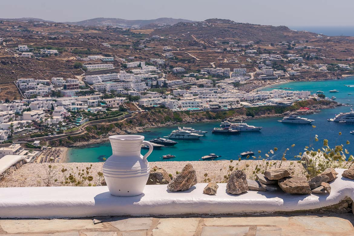 This is a view of Psarou Beach in Mykonos. The hill above the beach is excessively overbuilt with luxury villas while the sea is abundant in yachts.
