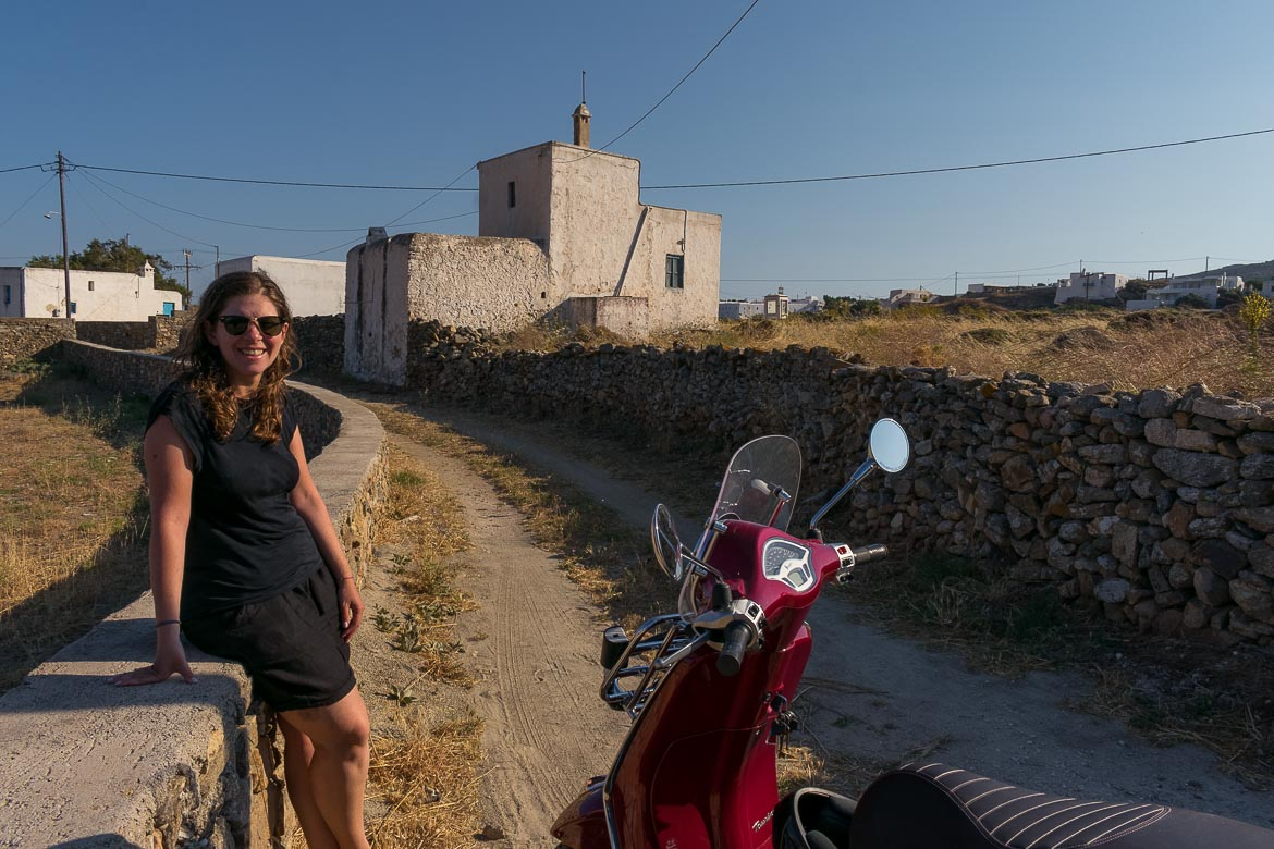 This image shows Katerina leaning on a low stone wall somewhere in the countryside of Mykonos. She is smiling. Her red vespa is parked next to her. In the background there are some old white buildings.