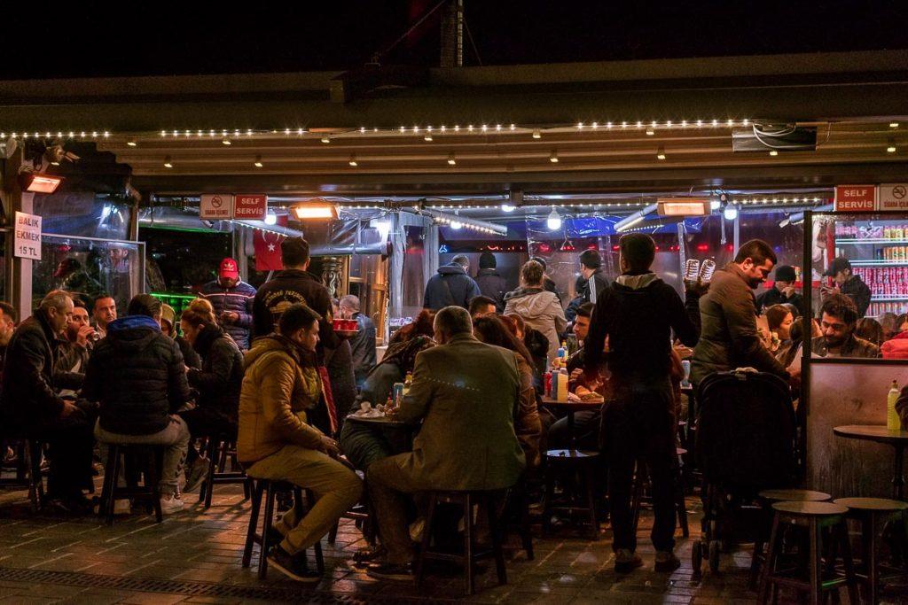 A balık ekmek restaurant packed with locals at night.