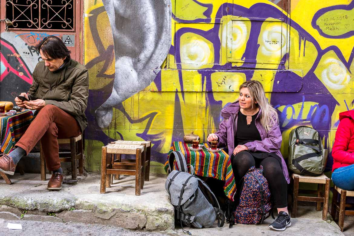 This photo shows Maria having a glass of tea at a traditional coffee shop. She is leaning against a wall with a colourful graffiti on it.