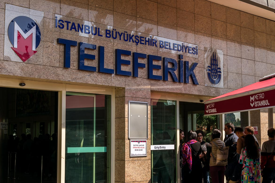 This is a photo of the entrance to the Teleferik. There is a long queue of people waiting to get on the cable car.