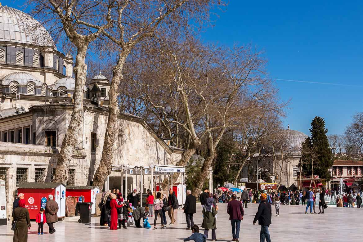 This photo shows the main square at Eyup. There are people walking or sitting and chatting. It's a bright spring day.