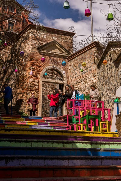 This image shows chairs painted in many bright colours on equally brightly coloured steps. It's a café in Fener.