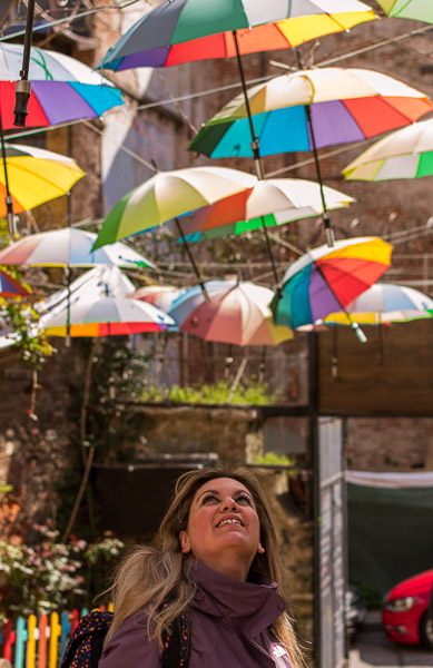 This photo shows many colourful umbrellas hanging above an outdoor cafe in Fener. Maria is standing below them, looking at them and smiling.