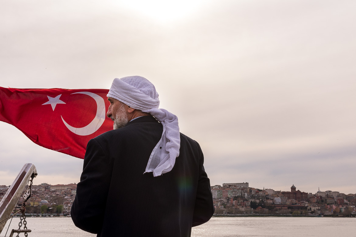 This photo shows a Turkish man enjoying the ferry ride. Next to him, the Turkish flag is moving with the wind.