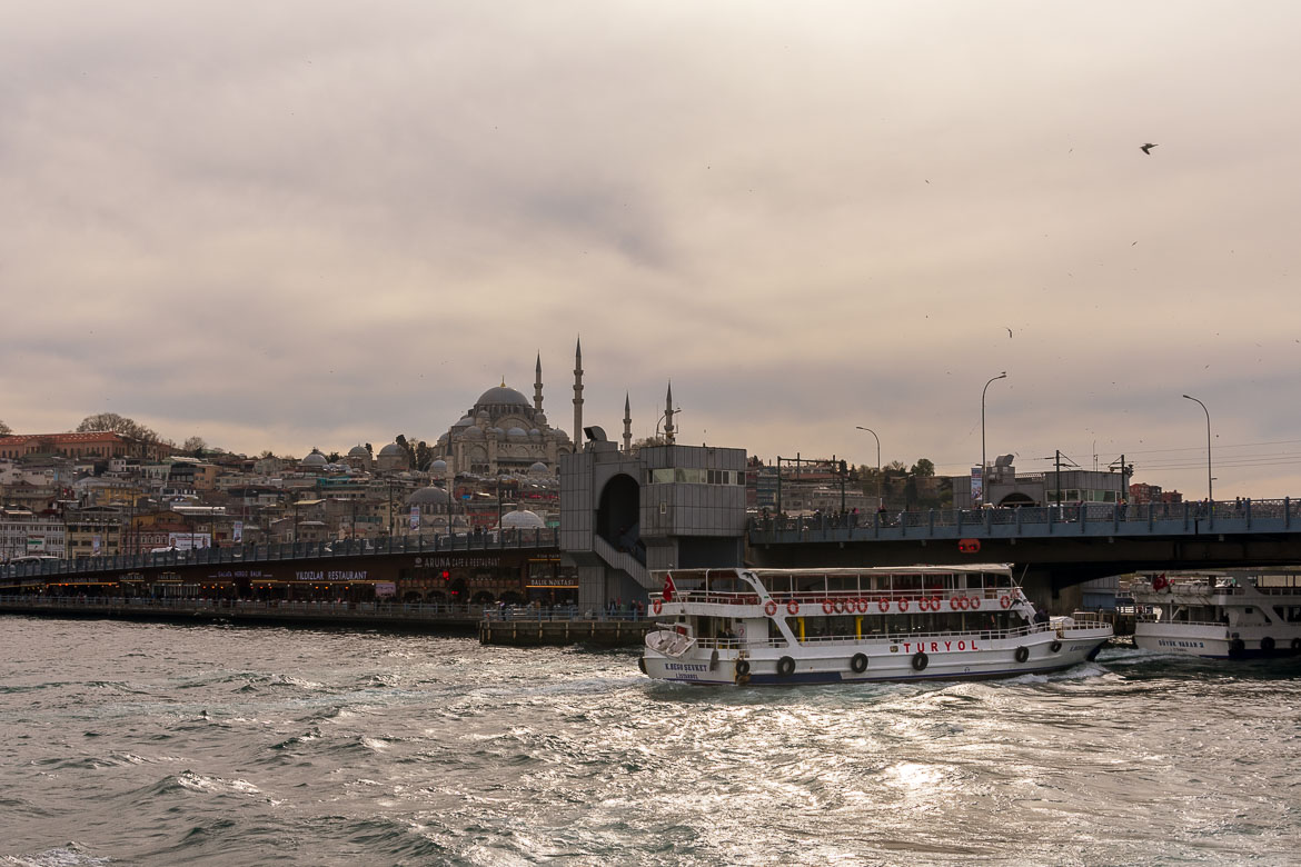 This photo shows a ferry sailing in front of Galata Bridge in Istanbul.