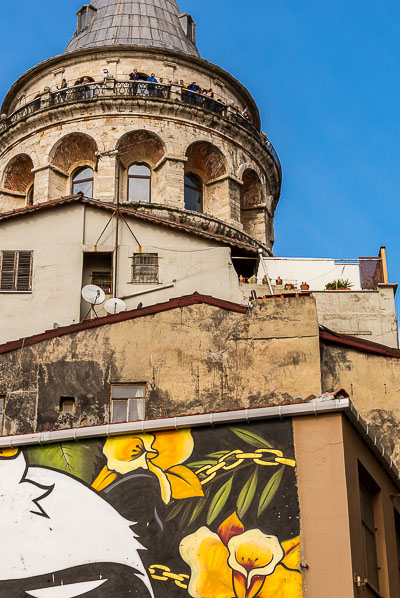 This image shows the Galata Tower. In front of the tower, there is a graffiti of vividly coloured flowers.