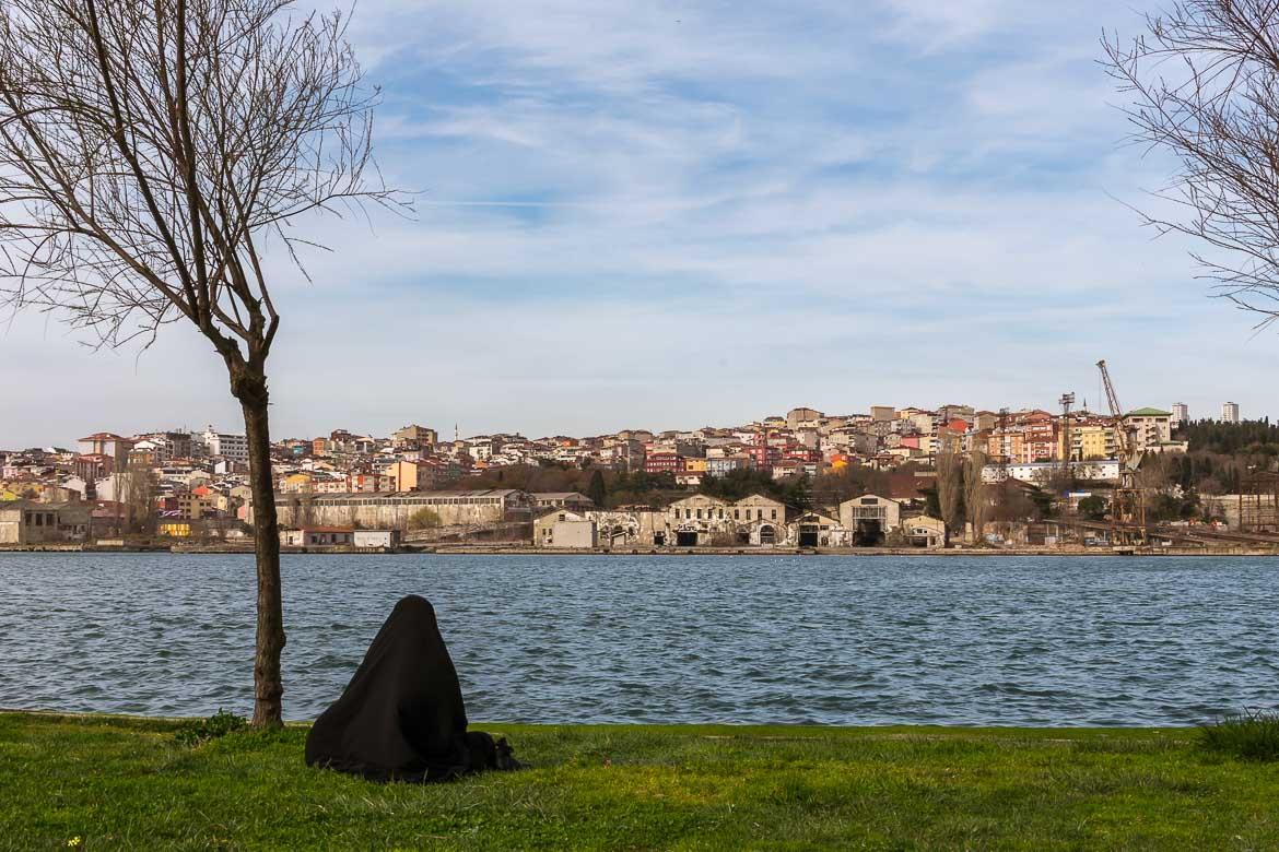 This photo shows a woman in traditional Muslim attire sitting on the grass next to the water along the Golden Horn. Her back is turned to the camera as she gazes at the city on the opposite shore.