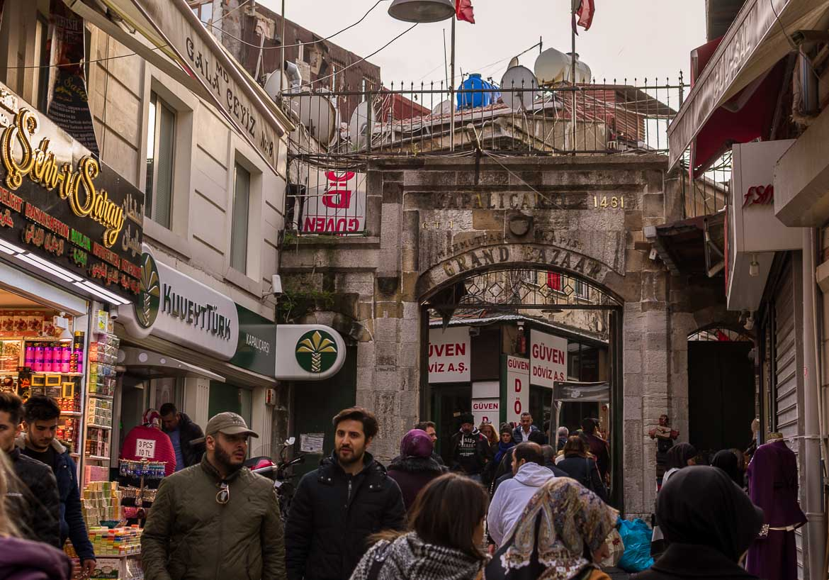 This photo shows the entrance to the Grand Bazaar. It is almost closing time and there are big crowds of shoppers or just passers by.