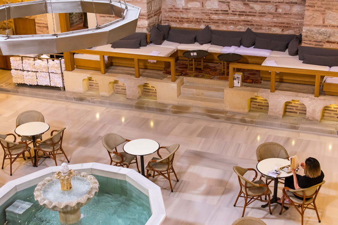 This photo shows the reception and welcoming area at Kilic Ali Pasa Hamami. The floors are made of marble and there is cosy furniture with wall to wall huge comfortable sofas. Everything is spotlessly clean. Enjoying a turkish bath was a highlight of our 5 days in Istanbul itinerary.