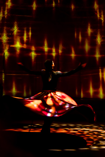 This photo shows a dancer performing the tanoura dance at the Hodjapasha Cultural Centre. The room is dark with just a few red and yellow lights. He is dressed in black except for his impressive red tanoura skirt. All this creates a mystic and gorgeous ambiance.