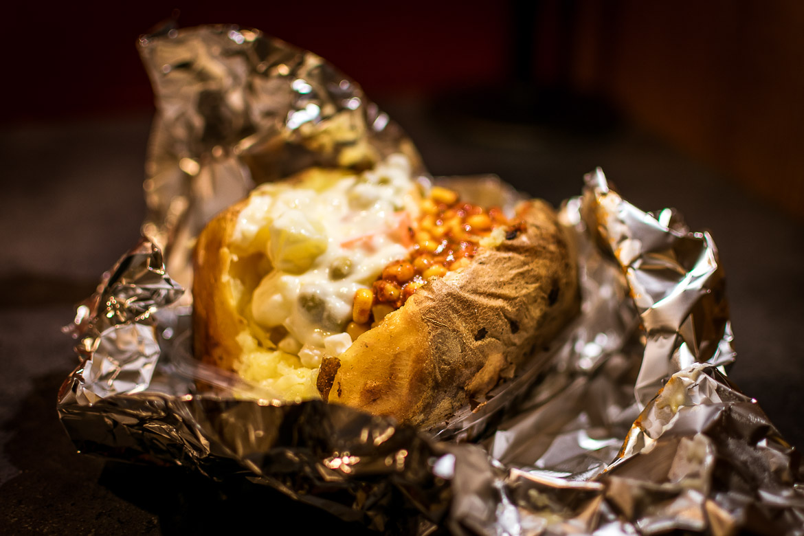 This is a close up to kumpir. A jacket potato filled with various ingredients such as corn, hot sauce, russian salad, olives and more.