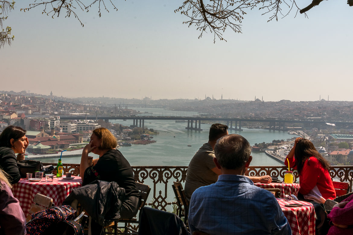 This is a photo of the café at Pierre Loti Hill.  It is a very quaint cafe with red and white checkered tablecloths. All tables are filled with people who enjoy the spring sun. In the distance, the silhouette of Istanbul is just gorgeous.
