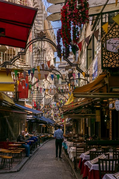 This is Nevizade Street. It is lined with tables and chairs, now empty, because this area comes to life in the evening. Colourful small flags and a big Turkish one hang above the street creating a festive ambiance.