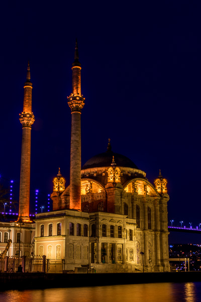 This photo shows Ortakoy Mosque at night. It is beautifully lit and in perfect harmony with the Bosphorus bridge right behind it.