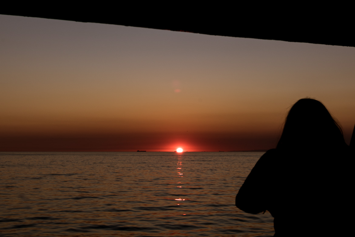 This photo shows the sun set in the sea. The photo was taken from on board the ferry at the Sea of Marmara.