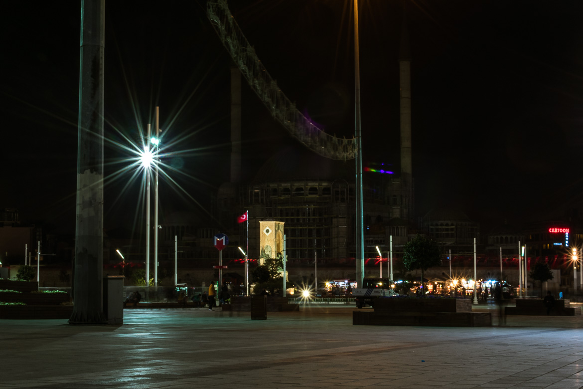 This is a photo of Taksim Square at night. The square is dimly lit and there are not many people around.