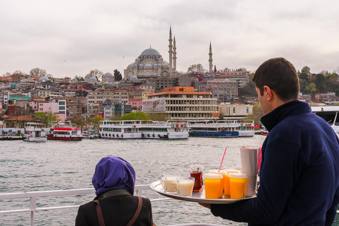 This photo shows a man serving tea and other refreshments on the Golden Horn ferry.