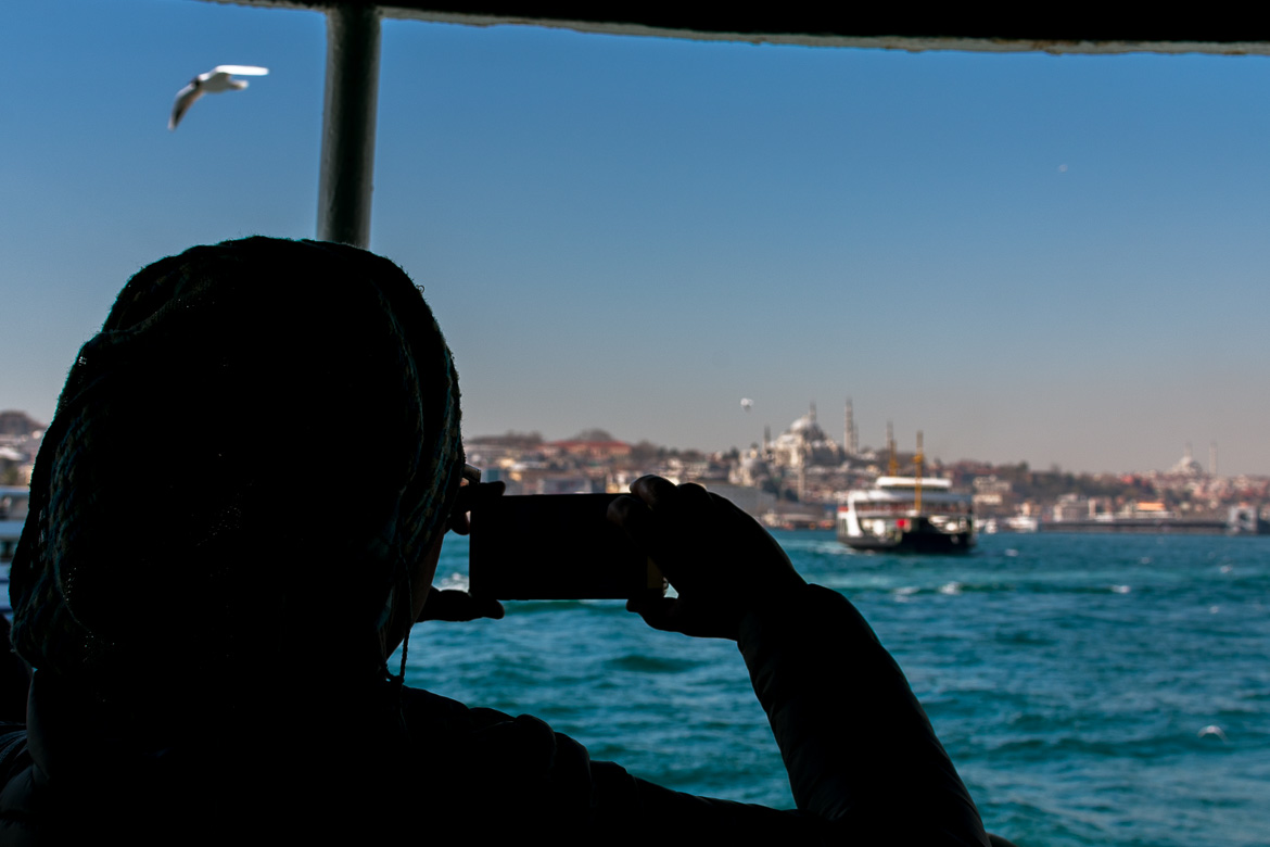 This is an image of a woman taking a photo of Istanbul from the ferry with her cellphone.
