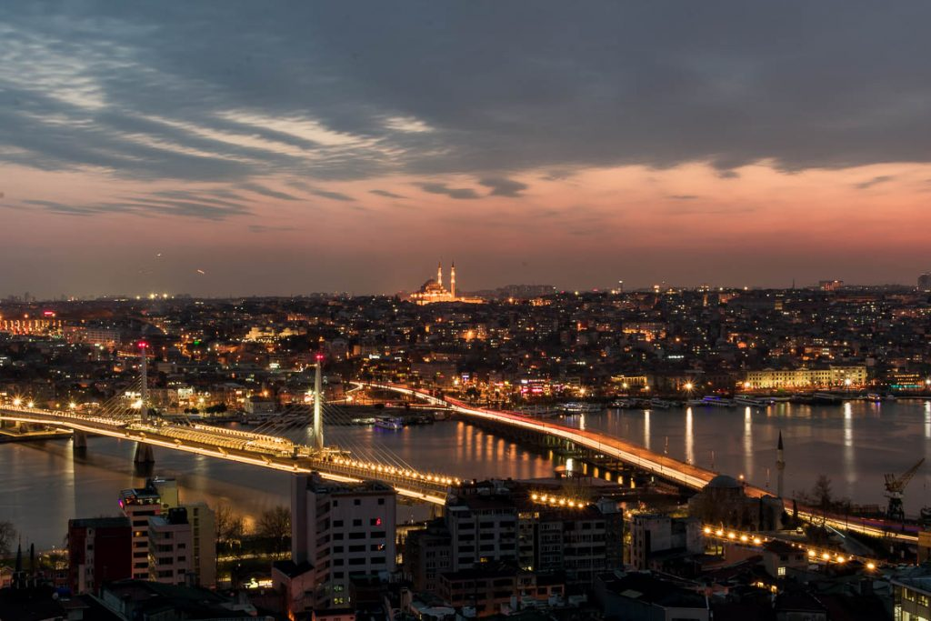 This photo was taken from the top of Galata Tower at sunset. The sky is pink and blue. In the distance, Suleymaniye mosque is lit and soars above the other buildings below. It's a panoramic view just as the city lights up. This is the photo we chose to be the featured image for our article: The best 5 days in Istanbul Itinerary + Guide
