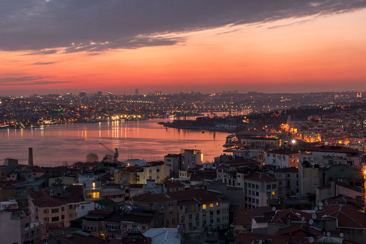 This photo shows the view from the top of Galata tower at sunset. The sky and sea are dyed in red as the city lights begin to become visible.