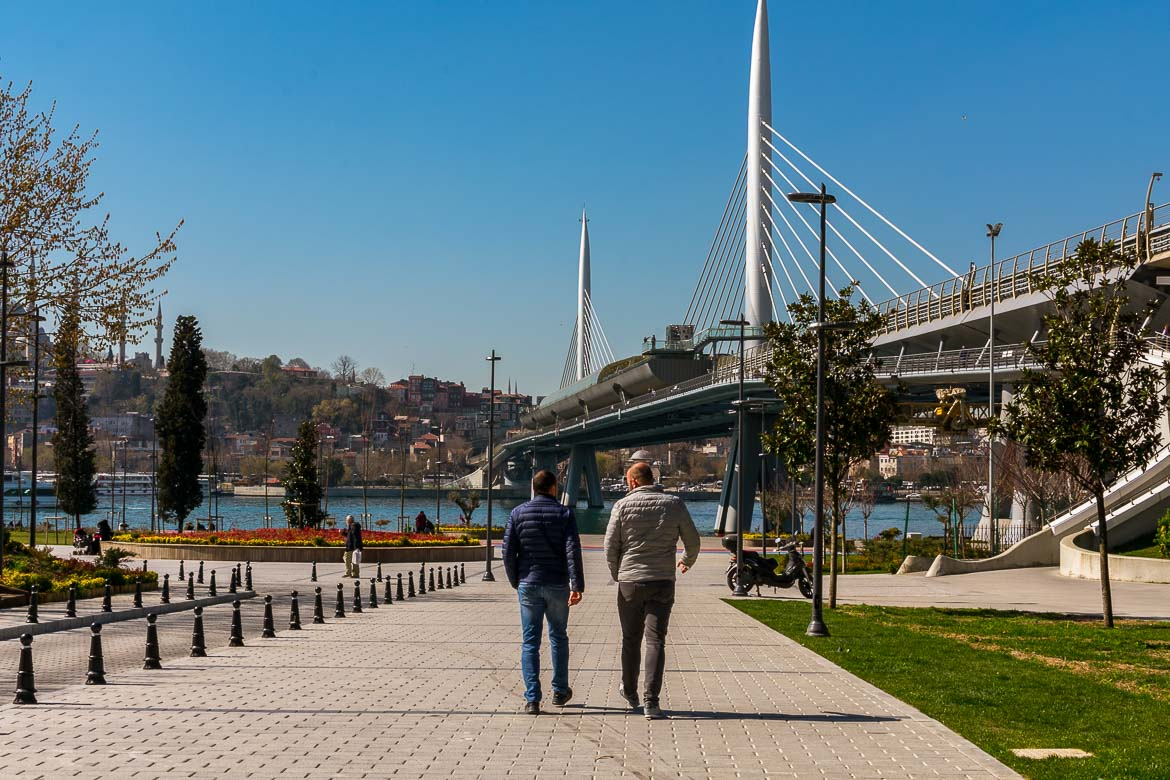 This photo shows two men walking along the pedestrianised path next to the Golden Horn Metro Bridge.