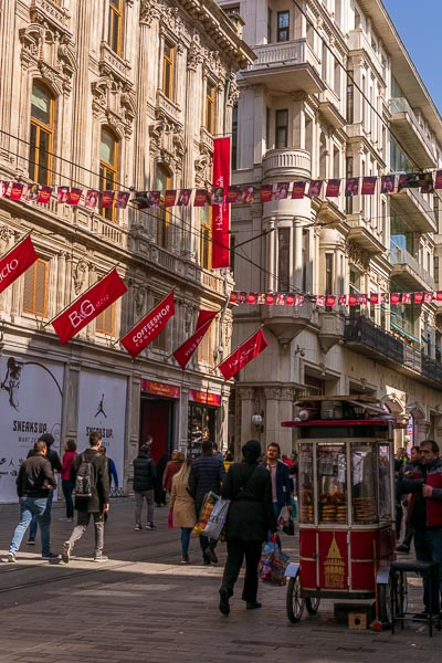 This photo shows a part of Istiklal Street. It is pedestrianised with grand buildings on both sides. In the middle of the street there is an iconic red cart selling Turkish snacks.