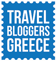 This is the logo of Travel Bloggers Greece. The three words are written in white capital letters on blue background.