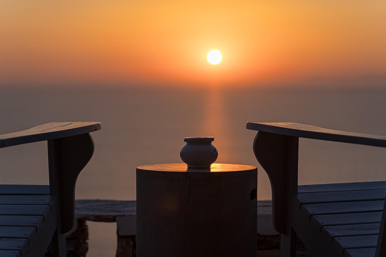 Τhis image shows the sun rising over the Aegean Sea. In the foreground, two wooden chairs and a table. If you're serious about travel photography, you need to be patient to catch the perfect shot.
