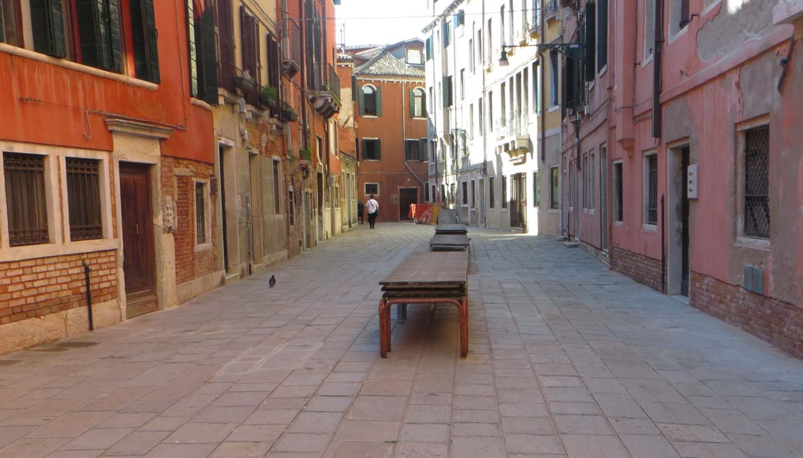 The photo shows the wooden platforms used in Venice, Italy during acqua alta sitting idly along the city's main streets when they are not needed. What to do in Venice: our complete guide to La Serenissima. It's all trip to me.