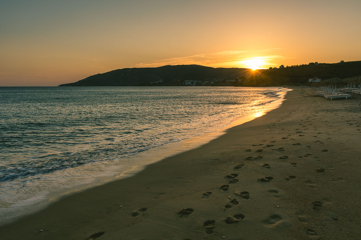 This photo shows Agios Petros beach on Andros island in the Cyclades Greece, during sunset. You can have a swim there after hiking on Andros island.