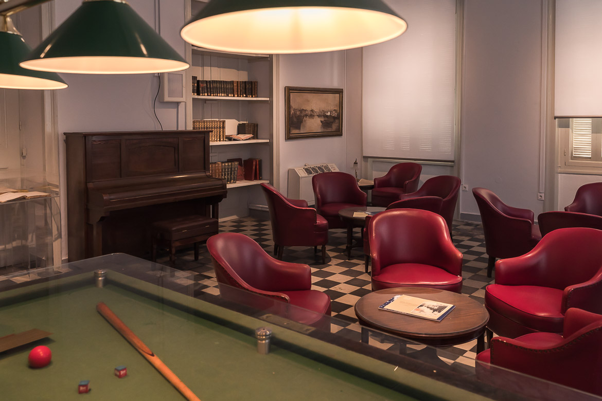 This image shows the interior of one of the rooms at Andrion Club. There are old-fashioned red armchairs and a French billiard table.