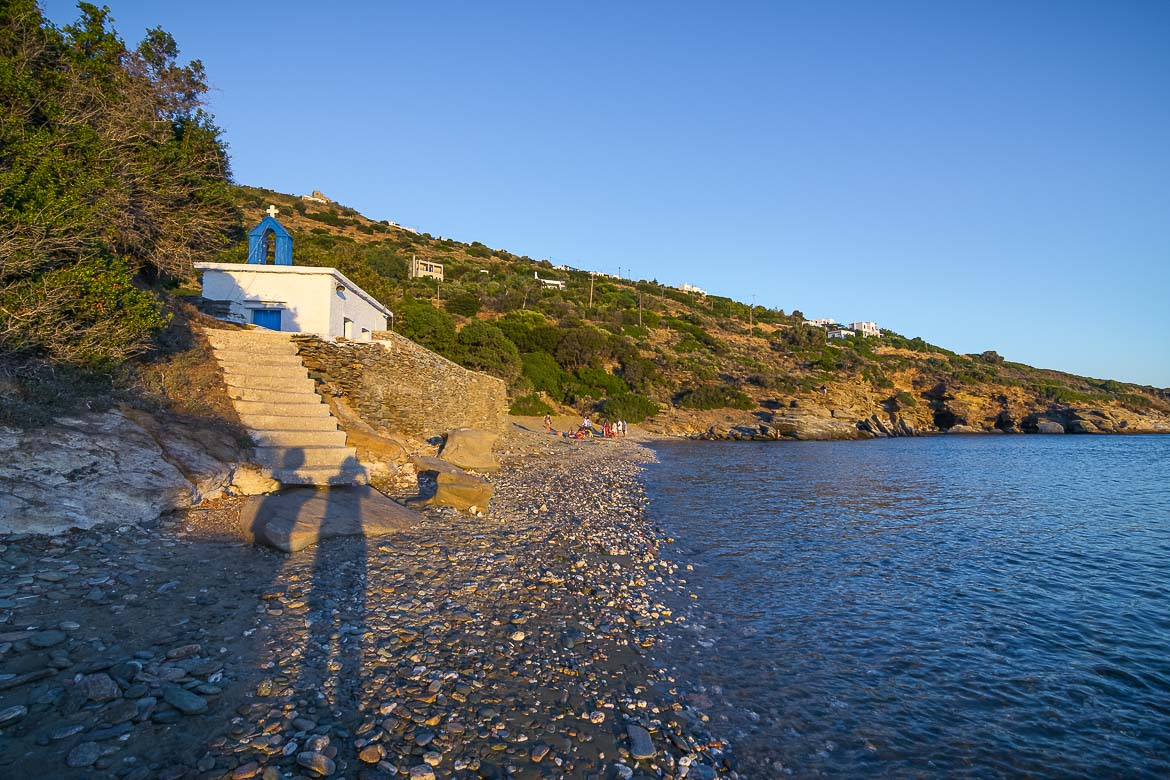 This image shows the tiny beach of Agios Kyprianos beach at sunset. We can see the shadows of Maria and Katerina as well as the quaint whitewashed chapel of Saint Kyprianos.