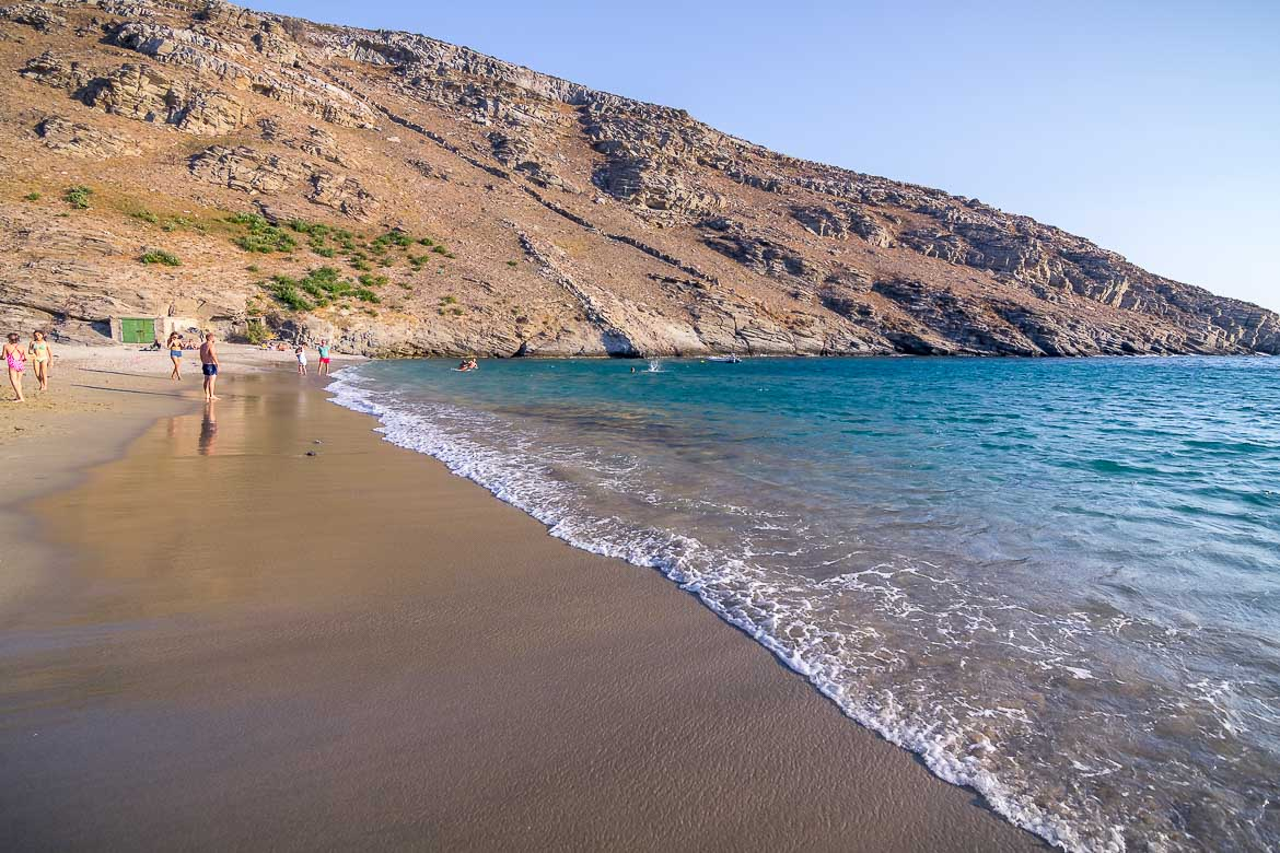 This image shows the turquoise waters of Apothikes beach as they embrace the golden sand.