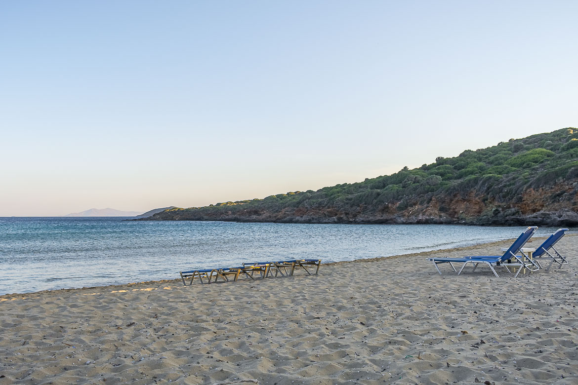 This image shows a handful of lonely sunbeds on the golden sand at Chryssi Ammos beach. There are no people around as it is pretty late in the afternoon.