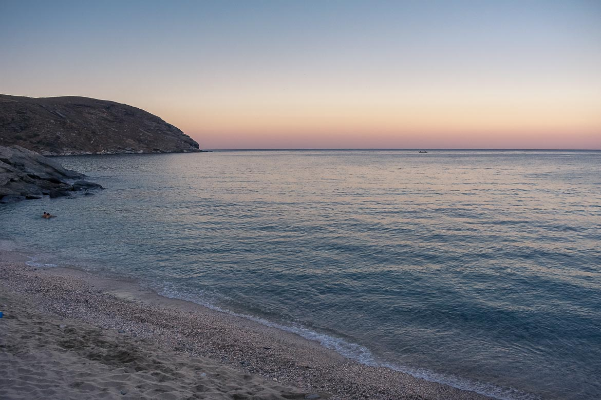 This is a shot of Gialia Beach at sunset. The sea is calm and the horizon is painted in pink.